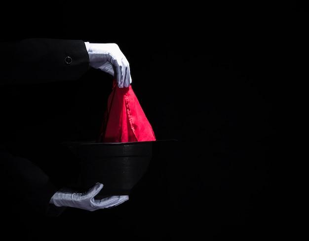 Die hand des zauberers, die magischen trick mit serviette über dem obersten schwarzen hut durchführt Kostenlose Fotos