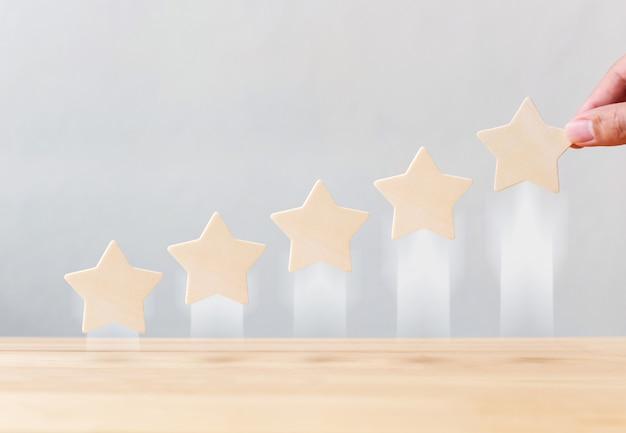 Die hand, die das wachsende wachstum der hölzernen form mit fünf sternen hält, erhöhen qualität auf tabelle. das beste konzept für die bewertung des kundenerlebnisses durch exzellente unternehmensdienstleistungen Premium Fotos