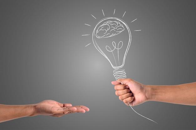Die hand, die die lampe hält, wird an die andere hand gesendet. Kostenlose Fotos