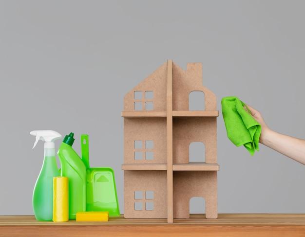 Die hand einer frau wäscht das symbolische haus mit einem grünen tuch neben dem haus - ein bunter satz von reinigungswerkzeugen. Premium Fotos