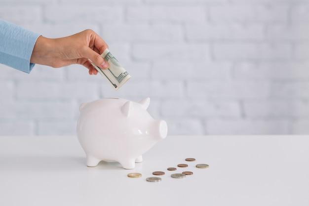 Die hand einer person, die banknote in weißes piggybank auf schreibtisch einfügt Kostenlose Fotos