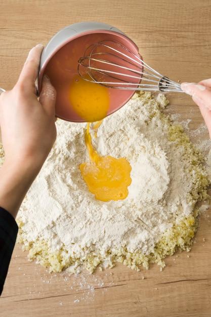 Die hand einer person, die die geschlagenen eier in das mehl und in den geriebenen käse für das zubereiten des italienischen gnocchi auf hölzernem schreibtisch gießt Kostenlose Fotos