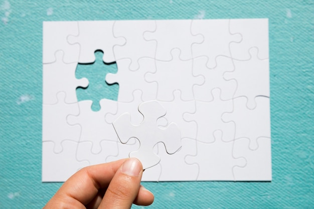 Die hand einer person, die weißes puzzlespielstück auf puzzlespielgitter über blauem strukturiertem hintergrund hält Kostenlose Fotos