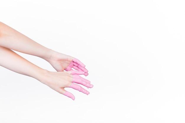 Die hand einer person mit rosa farbe über weißem hintergrund Kostenlose Fotos