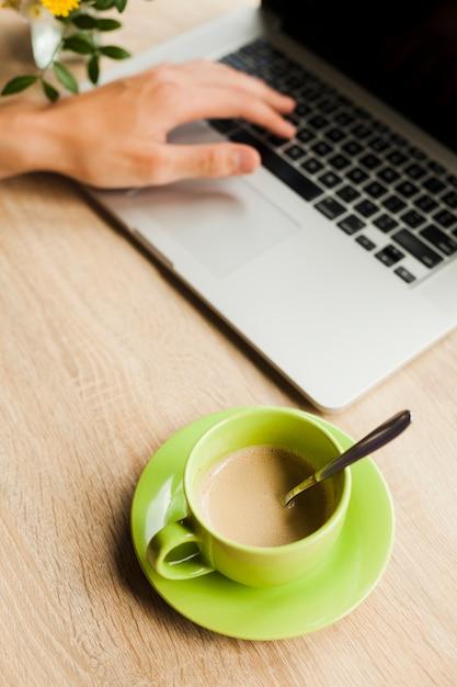 Die hand einer person unter verwendung des laptops mit tasse kaffee auf hölzernem schreibtisch Kostenlose Fotos