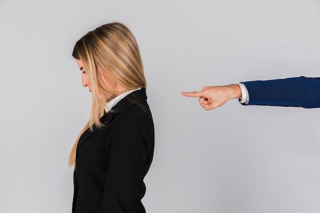 Die hand eines geschäftsmannes, die der jungen geschäftsfrau gegen grauen hintergrund die schuld gibt Kostenlose Fotos