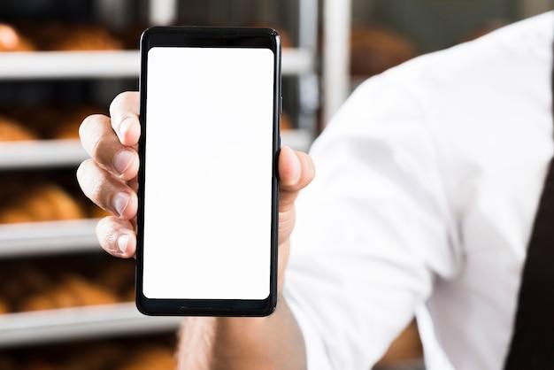 Die hand eines männlichen bäckers, die weiße bildschirmanzeige des handys zeigt Kostenlose Fotos