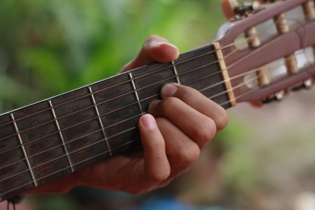 Die hand eines mannes, der gitarre und musik spielt Premium Fotos