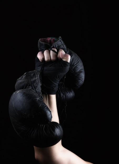 Die hand eines mannes hält ein paar alte schwarze boxhandschuhe aus leder Premium Fotos