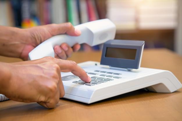 Die hand nimmt den hörer ab und drückt die taste am bürotelefon. Premium Fotos