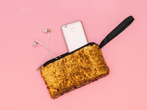 Die handtasche der frauen mit einem haftenden telefon und den kopfhörern der goldfarbe auf einer rosa tabelle. Premium Fotos