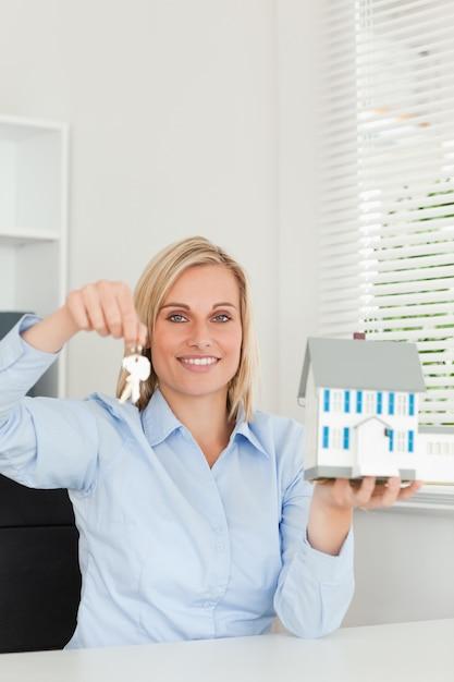Die herrliche blonde geschäftsfrau, die vorbildliches haus und schlüssel zeigt, untersucht kamera Premium Fotos