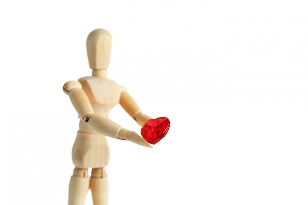 Die holzfigur eines mannes hält in seinen händen ein rotes herz auf einer weißen fläche, gibt das herz Premium Fotos