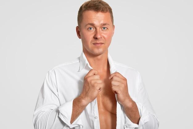 Die horizontale aufnahme eines ernsthaften attraktiven mannes trägt ein weißes hemd, zeigt seinen perfekten körper, hält sich fit, ist profisportler, hat eine gesunde haut und ist auf weiß isoliert. menschen- und sportkonzept Kostenlose Fotos