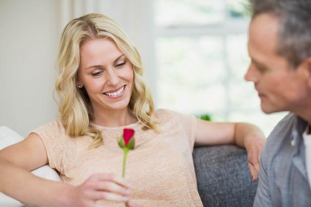 Die hübsche frau, die auf ihrer couch und ehemann sitzt, die eine rose im leben anbieten, stieg Premium Fotos