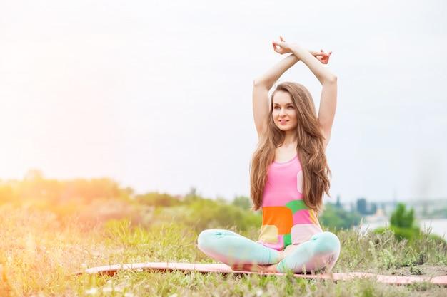 Die hübsche frau, die yoga tut, trainiert auf naturlandschaft Premium Fotos