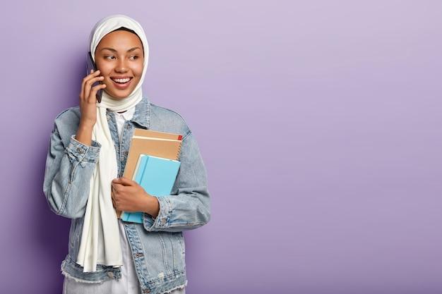 Die hübsche lächelnde araberin hat ein telefongespräch, schaut zur seite und bespricht die neuesten nachrichten mit dem gruppenmitglied über das handy Kostenlose Fotos