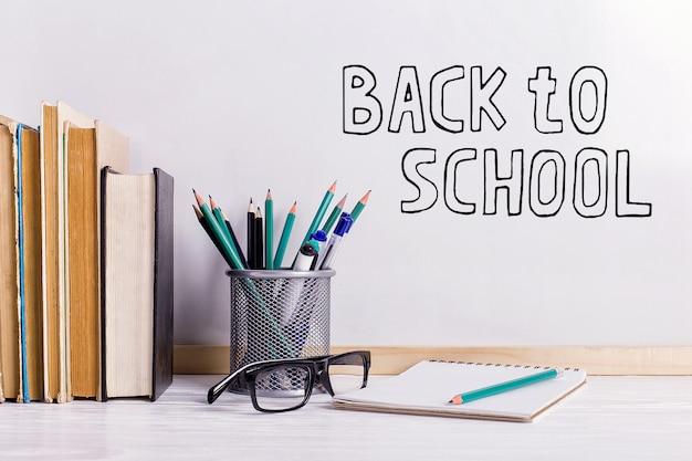 Die inschrift marker auf einer weißen tafel, back to school eine tabelle mit büchern und gläsern attribute zum schreiben. Premium Fotos