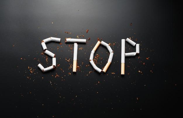 Die inschrift stop von zigaretten. aufhören zu rauchen. das konzept des rauchens tötet. motivationsschild zur raucherentwöhnung, ungesunde gewohnheit. Premium Fotos