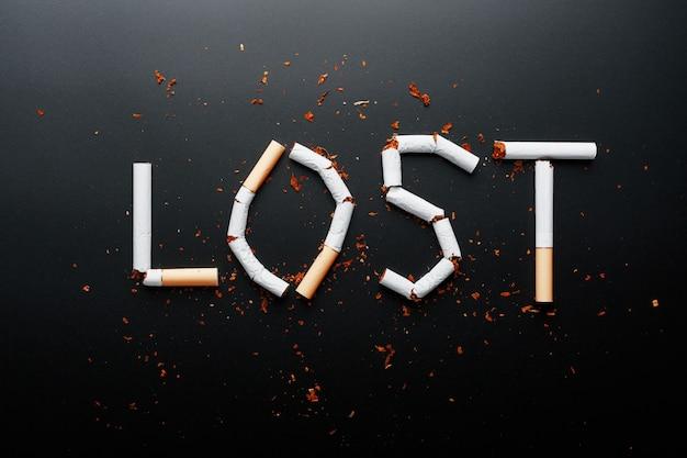 Die inschrift von zigaretten verloren. aufhören zu rauchen. das konzept des rauchens tötet. motivationsschild zur raucherentwöhnung, ungesunde gewohnheit. Premium Fotos
