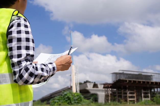 Die inspektoren oder ingenieure überprüfen die arbeit des auftragnehmerteams, um eine brücke über die straße zu bauen. Premium Fotos