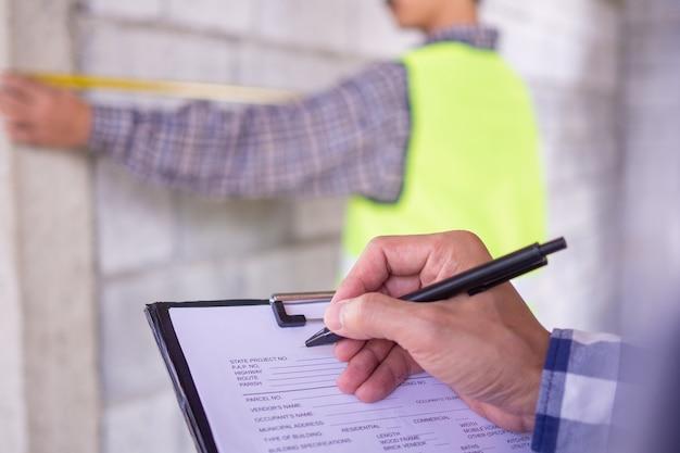 Die inspektoren überprüfen das hausprojekt, für das die immobilie mit dem auftragnehmer beauftragt wurde. beachten sie auch die arbeitsdetails, um gemäß dem muster bereit und korrekt zu sein. Premium Fotos