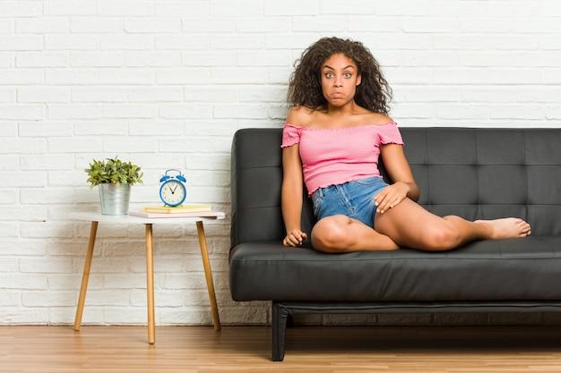 Die junge afroamerikanerfrau, die auf dem sofa sitzt, zuckt die schultern und die offenen augen, die verwirrt werden. Premium Fotos