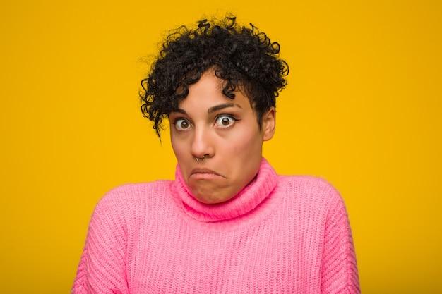 Die junge afroamerikanerfrau, die eine rosa strickjacke trägt, zuckt die verwirrten schultern und offenen augen. Premium Fotos