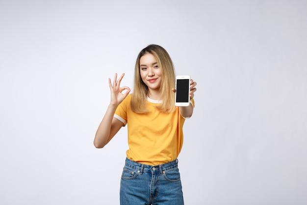 Die junge asiatin, die im gelben hemd trägt, zeigt okayzeichen auf weißem hintergrund Premium Fotos