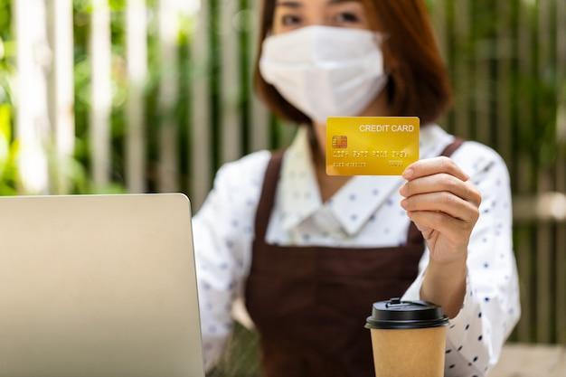 Die junge asiatische geschäftsfrau besitzt ein café mit einem tablet und einer kreditkarte, um den kunden zu sagen, dass sie für den gesamten service bar bezahlen sollen Premium Fotos