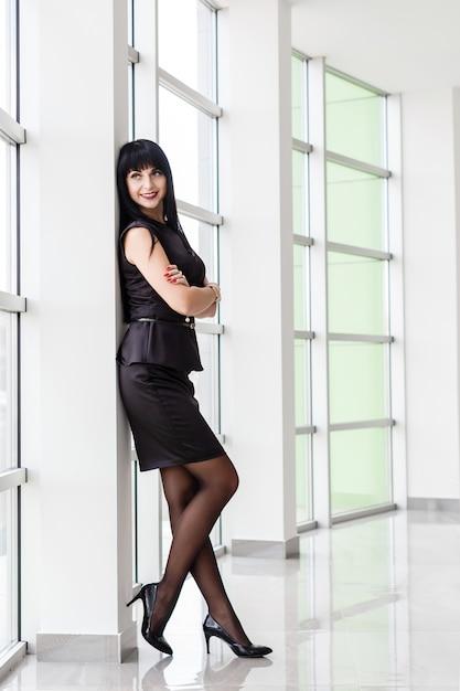 Die junge attraktive glückliche brunettefrau, die in einem schwarzen anzug mit einem kurzen rock gekleidet wird, steht nahe dem fenster in einem weißen büro und lächelt. Premium Fotos
