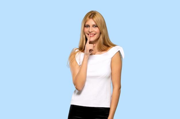 Die junge blonde frau, die ein zeichen der ruhegeste auf lokalisiertem blauem hintergrund zeigt Premium Fotos