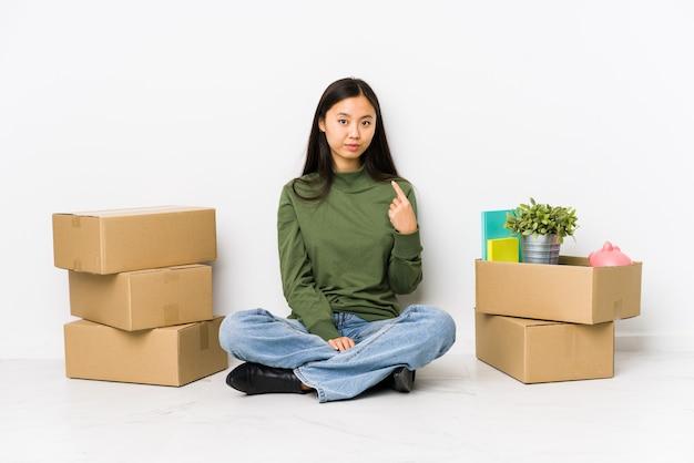 Die junge chinesische frau, die auf ein neues haus zeigt mit dem finger auf sie umzieht, als ob einladung näher kommen. Premium Fotos