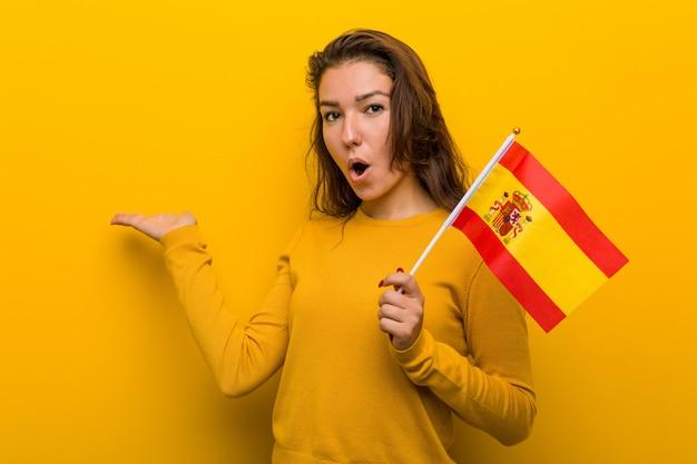 Die junge europäische frau, die eine spanische flagge hält, beeindruckte das halten von copyspace palme. Premium Fotos