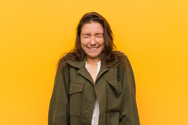 Die junge europäische frau, die über gelbem hintergrund lokalisiert wird, lacht und schließt augen, fühlt sich entspannt und glücklich. Premium Fotos