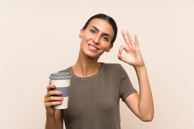 Die junge frau, die ein hält, nehmen den kaffee weg, der okayzeichen mit den fingern zeigt Premium Fotos