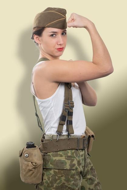 Die junge frau, die in der amerikanischen militäruniform ww2 gekleidet wird, zeigen ihr bizeps Premium Fotos