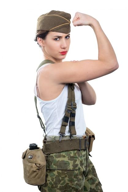 Die junge frau, die in der wwii-militäruniform gekleidet wird, zeigen ihr bizeps Premium Fotos