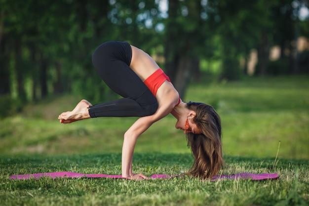 Die junge frau, die yoga tut, trainiert im sommerstadtpark Premium Fotos