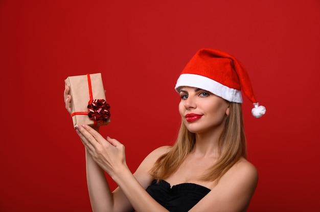 Die junge frau in einer weihnachtsmütze hält ein weihnachtsgeschenk. Premium Fotos