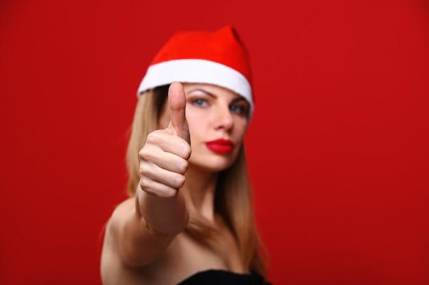 Die junge frau in einer weihnachtsmütze lächelt und zeigt ihren daumen. das konzept von weihnachten. Premium Fotos