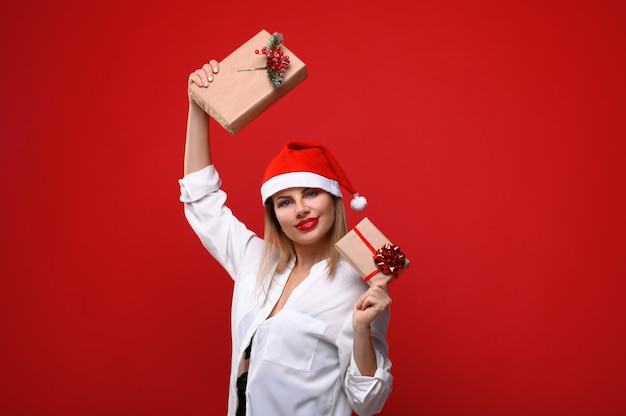 Die junge frau in einer weihnachtsmütze mit weihnachtsgeschenken in der hand. Premium Fotos