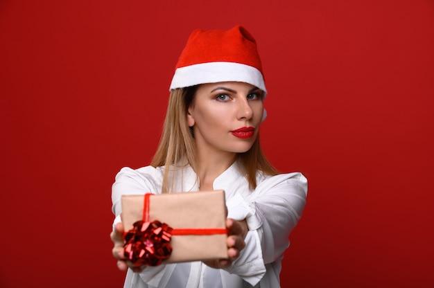 Die junge frau in einer weihnachtsmütze zeigt der kamera ein weihnachtsgeschenk. konzentrieren sie sich auf das modell. Premium Fotos
