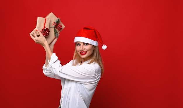 Die junge frau in einer weihnachtsmütze zeigt weihnachtsgeschenke steigend und hoch. Premium Fotos