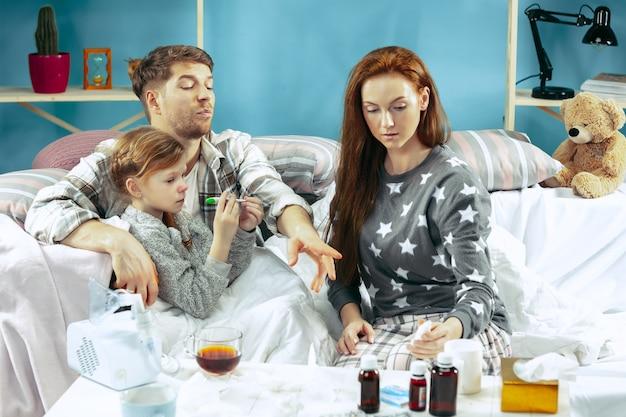 Die junge frau und der mann mit der kranken tochter zu hause. behandlung zu hause. familienhaftigkeit. Kostenlose Fotos