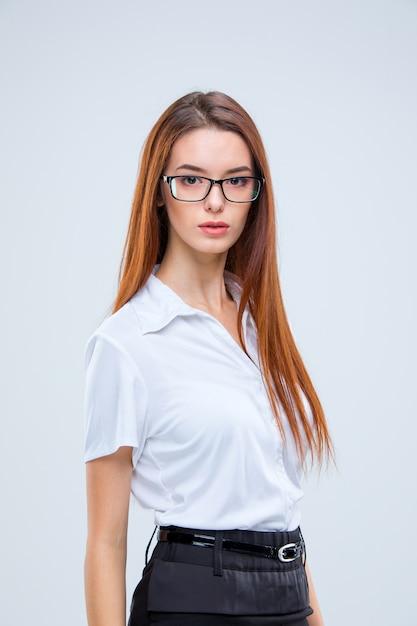 Die junge geschäftsfrau in gläsern auf einem grau Kostenlose Fotos