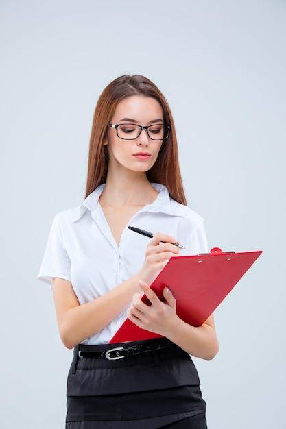 Die junge geschäftsfrau in gläsern mit stift und tablette für notizen auf einem grau Kostenlose Fotos
