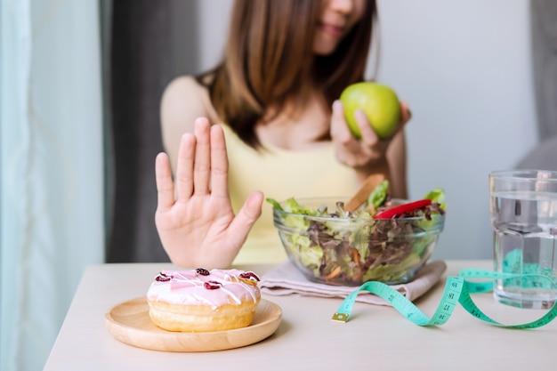 Die junge gesunde frau, die hand verwendet, drücken nachtisch und bonbons aus und wählen grünen apfel und frisches salat-, gesundenlebensstil- und diätkonzept Premium Fotos