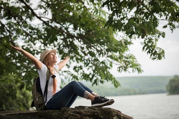 Die junge glückliche frau, die mit rucksack sitzt, genießen die natur nach wanderung. Kostenlose Fotos