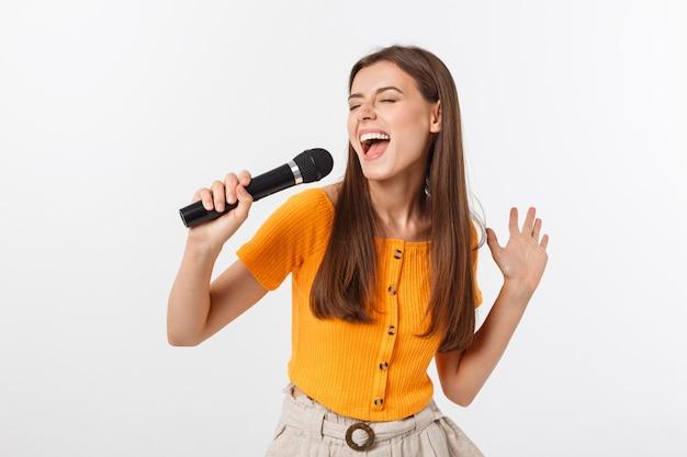 Die junge hübsche frau, die glücklich und motiviert ist, ein lied mit einem mikrofon singt, ein ereignis darstellt oder eine partei hat, genießen den moment Premium Fotos